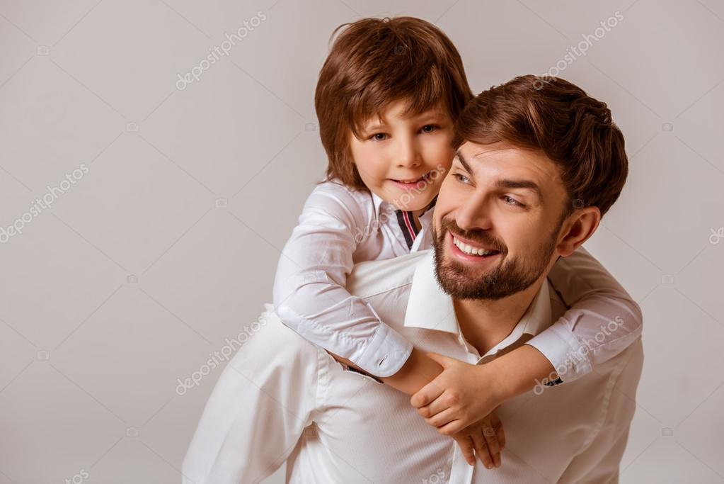 adca0bfe59ddef Ritratto di un padre bello portando suo figlio sveglio sul retro e  sorridente. Entrambi in camicia bianca classica, in piedi su uno sfondo  grigio — Foto di ...