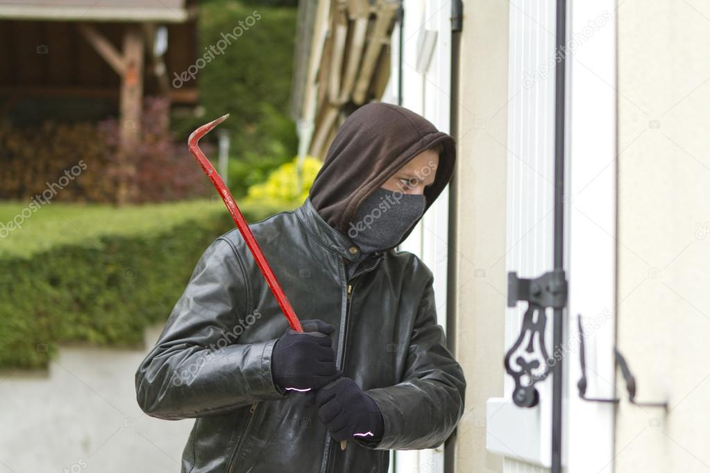 Burglar wearing black clothes and leather coat breaking in a house