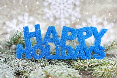 Inscription of happy holidays with spruce branches with frost