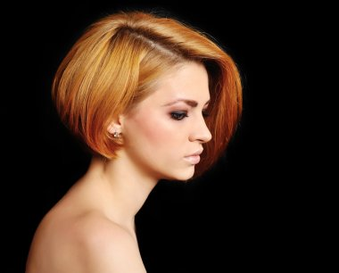Red hair. Beautiful Woman with Short Hair on a black background.
