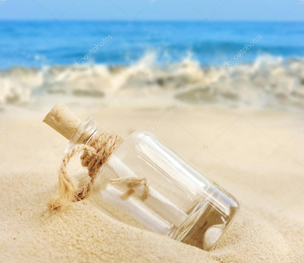 a letter in a bottle on the beach photo by nataliiamelnyc