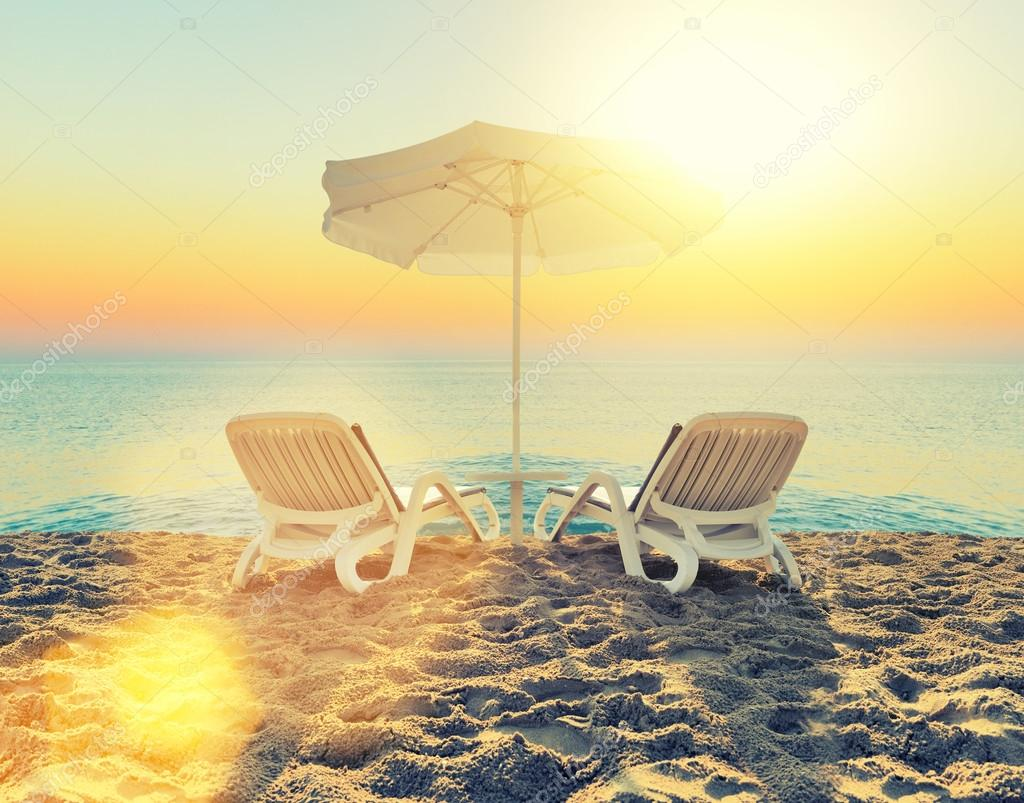 Beach chair and white umbrella on beach