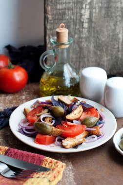 Italian Panzanella salad with bread, tomatoes, basil, capers and olive oil on rustic style