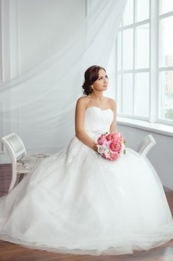 The Bride. Young women with wedding dress in very bright room,
