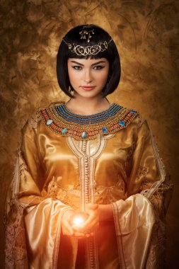 Beautiful Egyptian woman like Cleopatra with magic ball on golden background