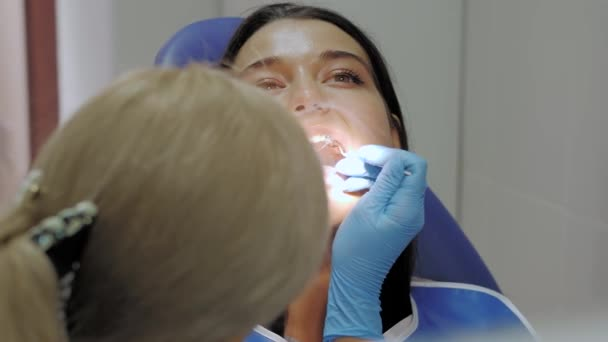 Dentist doing a dental treatment on a female patient.