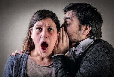 Man whispering something in the ear