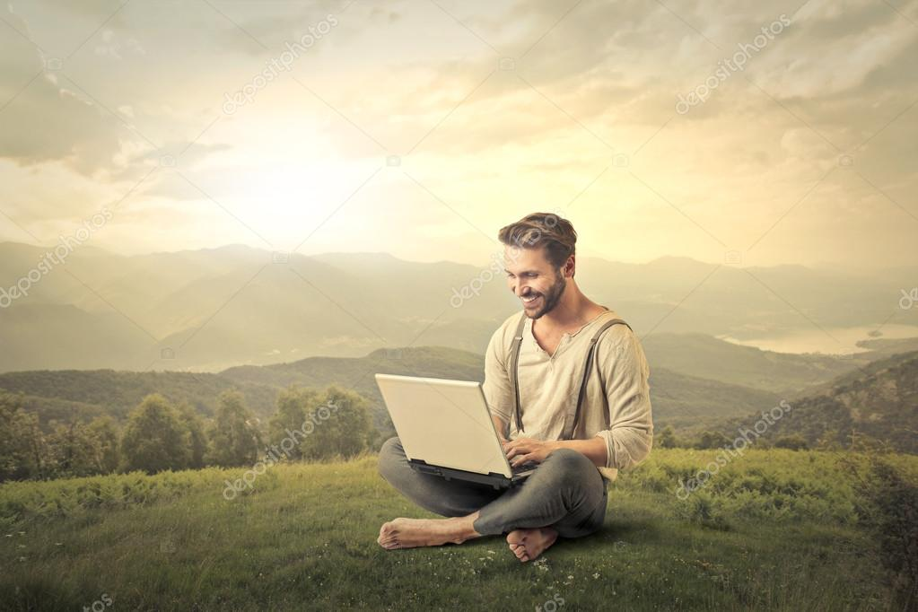 Man working with his computer at the countryside