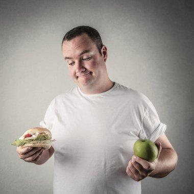 Chubby man deciding whether to eat healthy food or a hamburger