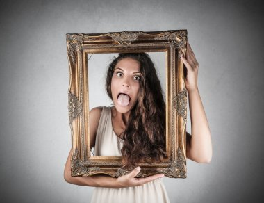 Beautiful girl holding a frame and stucking her tongue out
