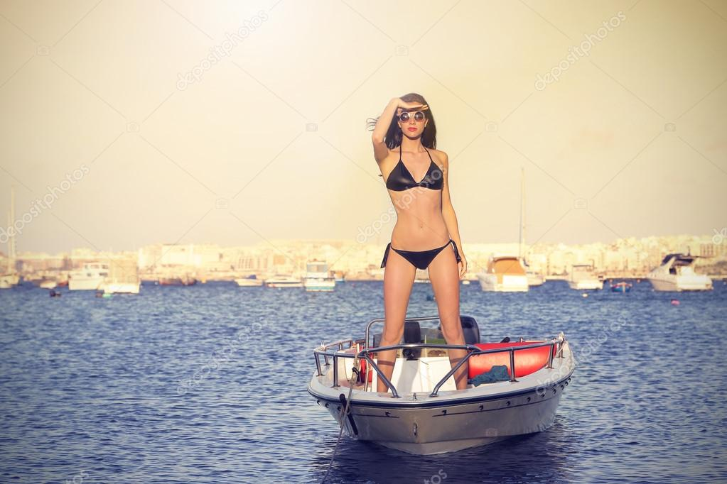 Beautiful woman standing on a little boat in the water