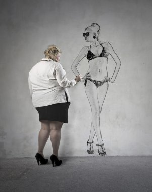 Chubby woman drawing a model on a wall
