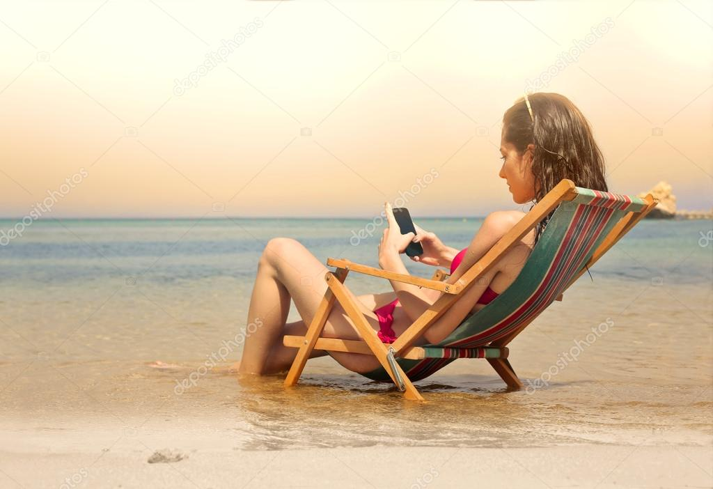 Young woman sitting in a beach chair sending a text message