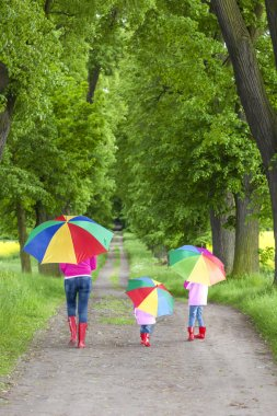 Mother and her daughters with umbrellas