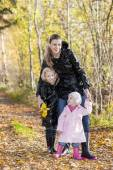 Fotografie mother with her daughters in autumnal nature