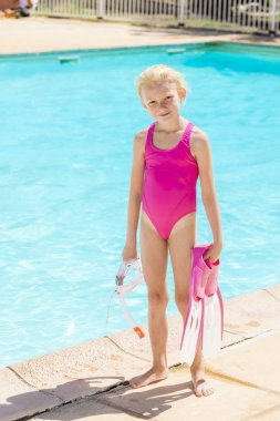 little girl with snorkeling equipment at swimming pool