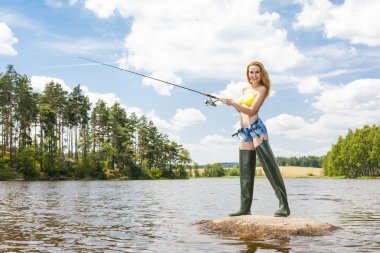 woman fishing in pond during summer
