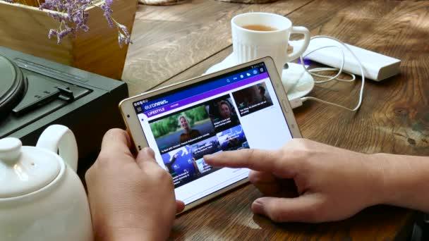 Muž navštíví web euronews v tablet pc v kavárně