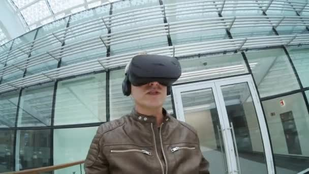 Man in VR headset talking at camera in modern building