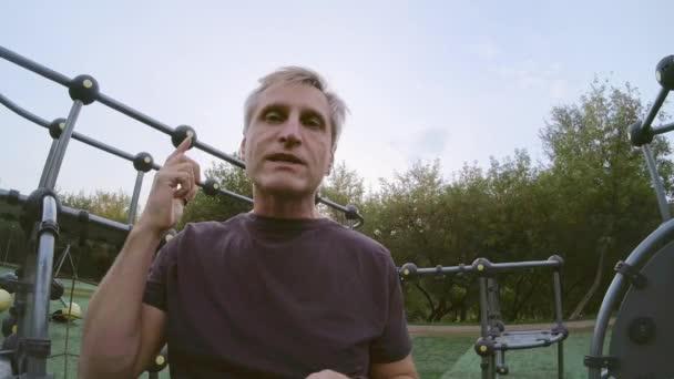 Mature man talking at camera on sports ground