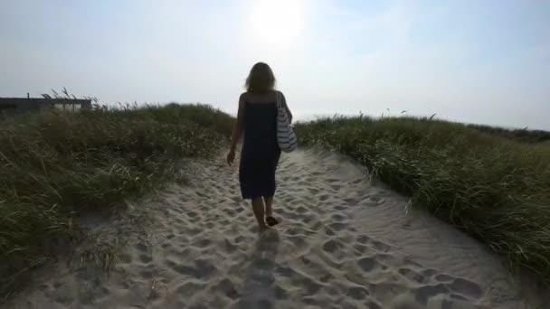 Unrecognizable woman walking on path on seashore
