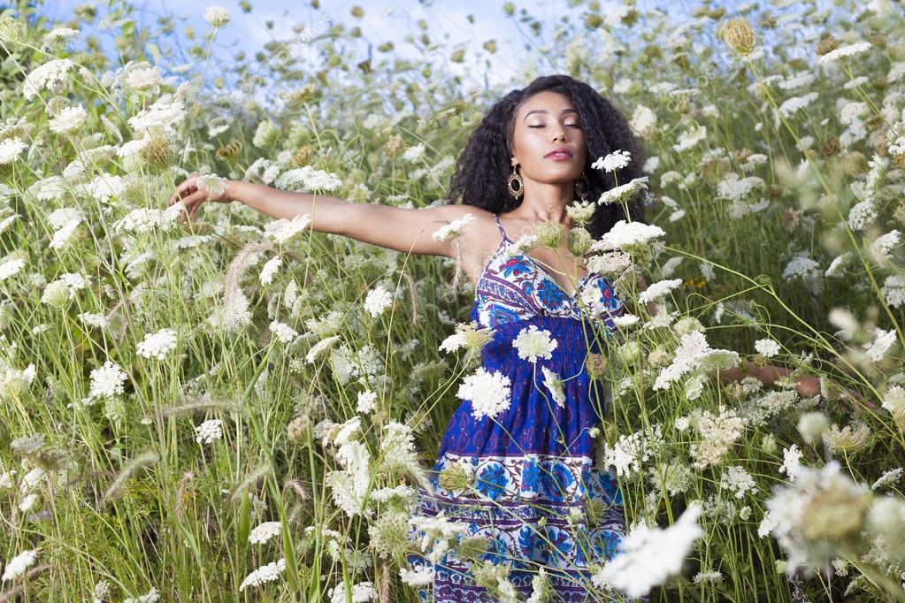 Girl enjoys hot summer day on flower field.