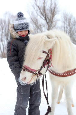 Pretty little winter child with horse