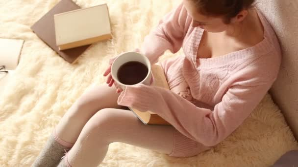 fiatal nő, egy könyvet olvas, és kávét iszik