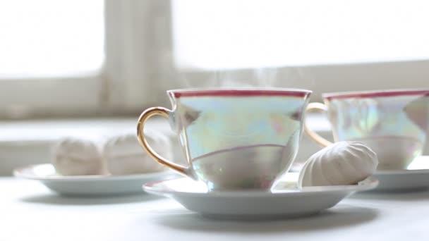 Dva šálky horkého čaje a zákusek na stůl