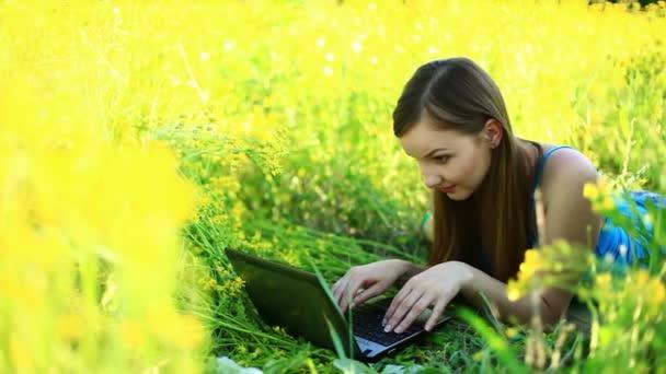 Mladá dáma s notebookem v trávě