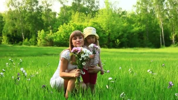 Young mother and child with flowers in the field