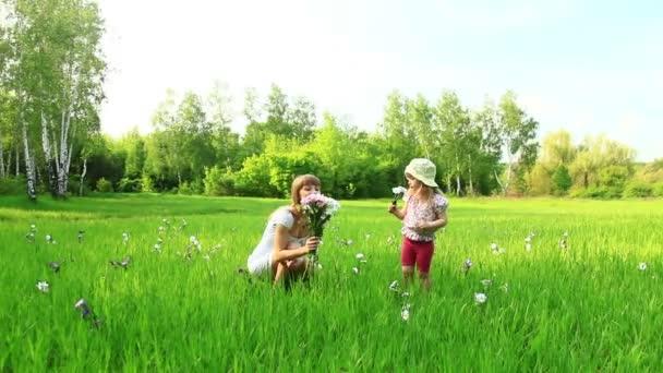 Mladá matka a dítě s květinami v poli