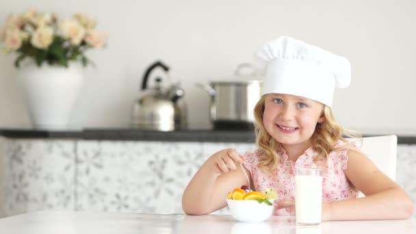 Mädchen isst Joghurt und trinkt Milch