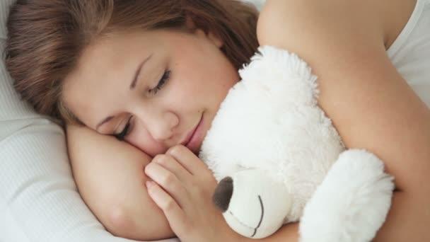 Alvó lány átölelve mackó