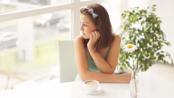 žena sedí u stolu s kávou
