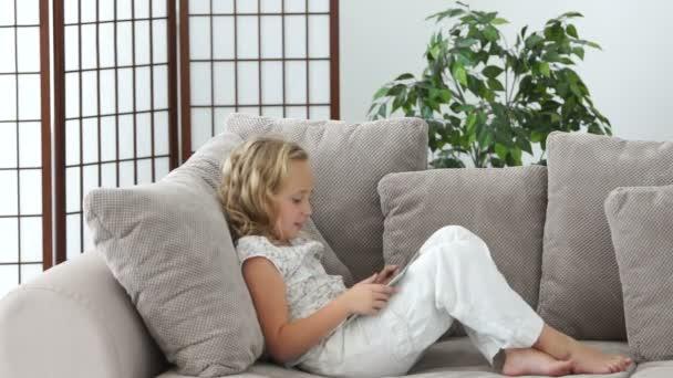 Holčička na gauči s tablet pc