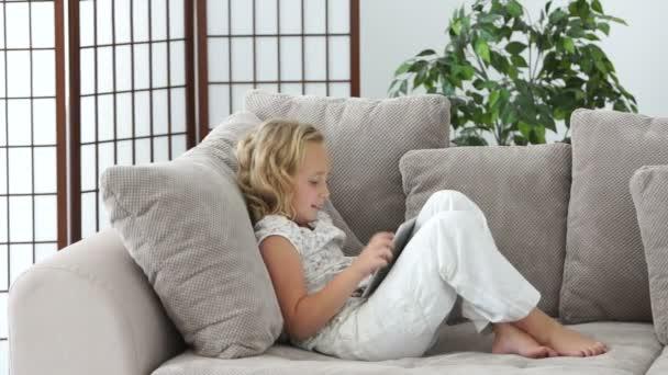 Ospalá dívka na pohovce s tablet pc
