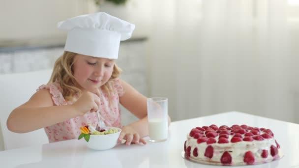 Mädchen mit Hut isst Joghurt