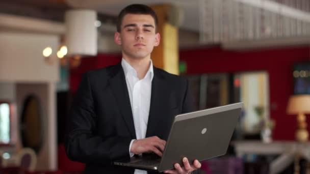 Muž, který stojí v kavárně s notebookem