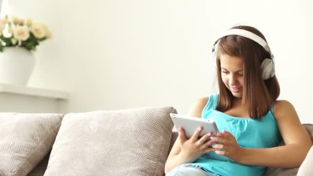 girl in headset sitting on sofa