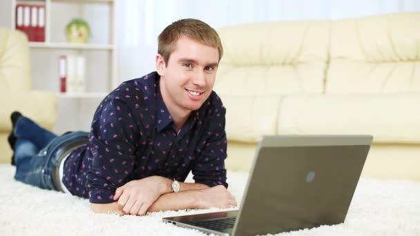 muž leží na koberci s notebookem