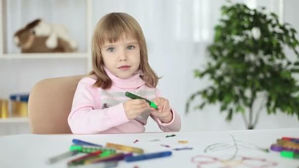 Bambino a un tavolo che guarda lobbiettivo