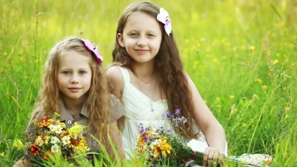 Schwestern sitzen auf dem Gras