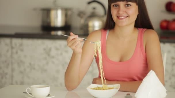 dívka sedí u kuchyňského stolu a jíst