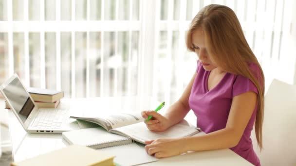 dívka sedí u stolu s knihami