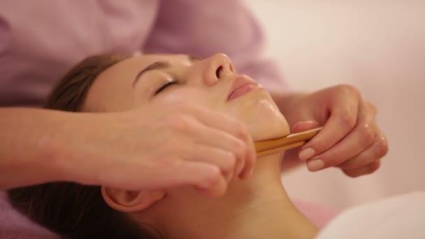 terapeut dělá masáž ženského obličeje
