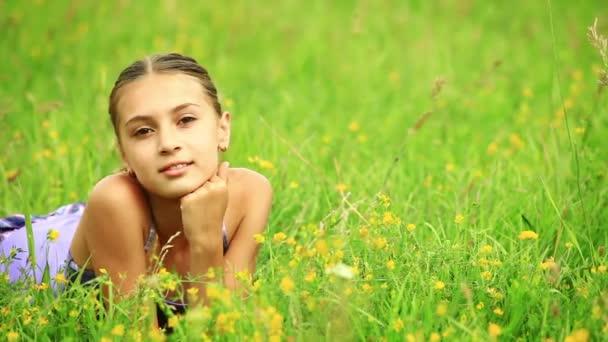 dívka ležící na trávě.