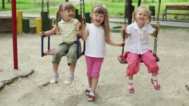 girls laughing on a swing