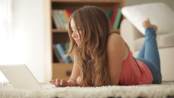 dívka ležela na podlaze pomocí přenosného počítače