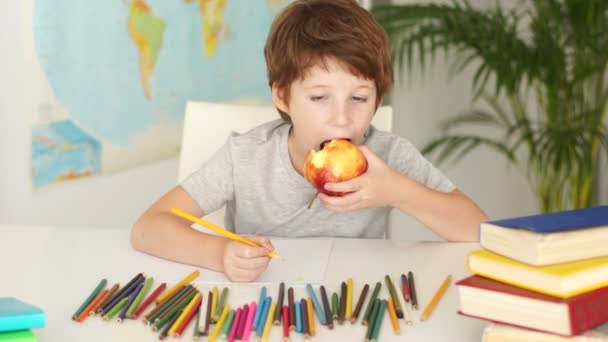 boy sitting at table holding apple